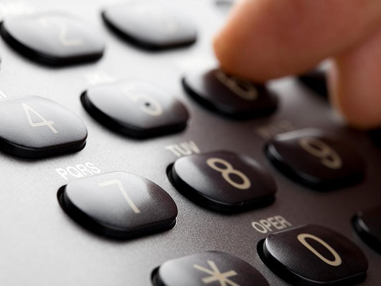 palec dłoni wciskający przyciski natelefonier